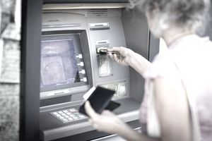 Mature woman inserting credit card into local french cash machine