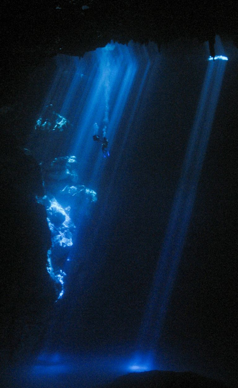 Vertical shafts of aquamarine light plunge more than 100 feet down through the cenote cavern at the Pit, illuminating divers on a spectacular cenote scuba dive.
