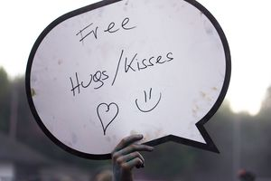 A paint covered hand holding a free hugs shield at holi festival.