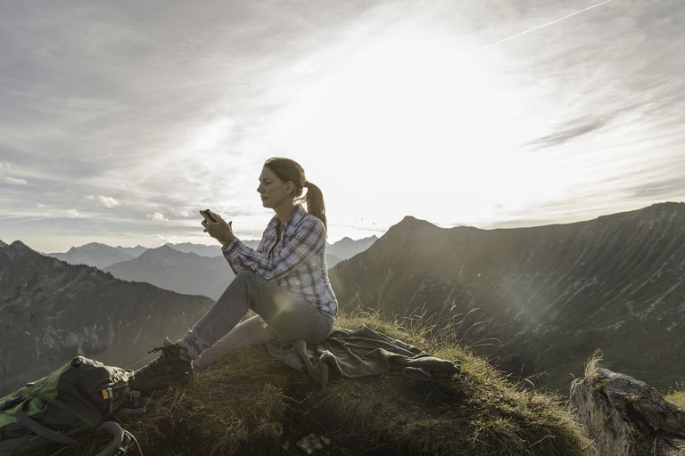 Portrait of a mid adult woman backpacker using smartphone, Achensee, Tyrol, Austria