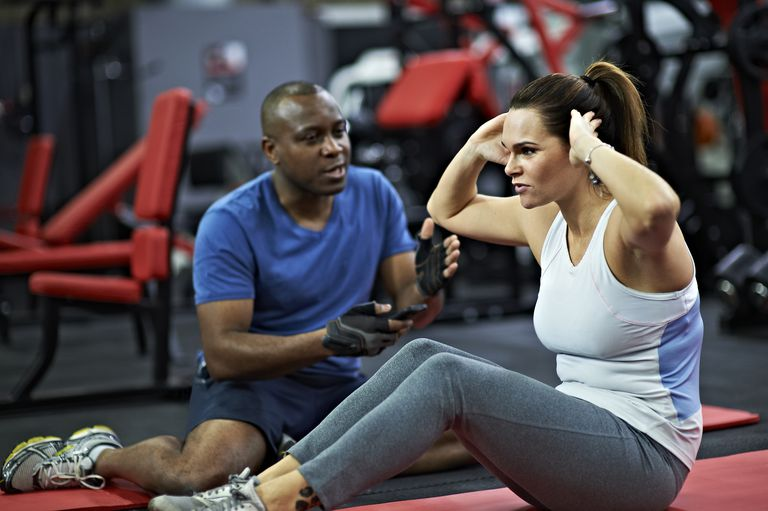An exercising woman is flexing her spine while seated.
