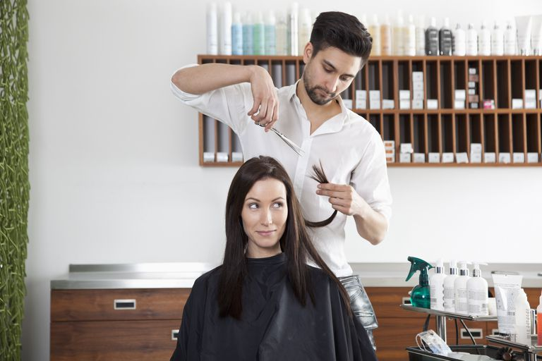 A woman having her hair cut by a male hairdresser