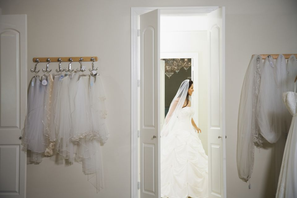Hispanic bride in wedding gown at dress shop