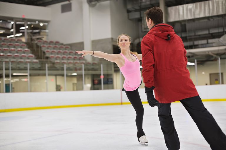 Female figure skater with coach practicing routine in skating rink.