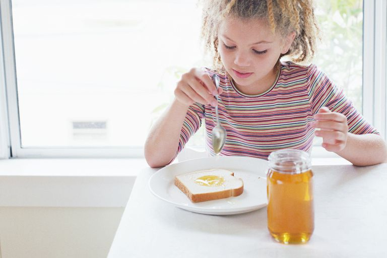 Girl (8-10) putting honey on slice of bread