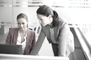 Two women work on learning the new Human Resources Management Information System (HRIS)