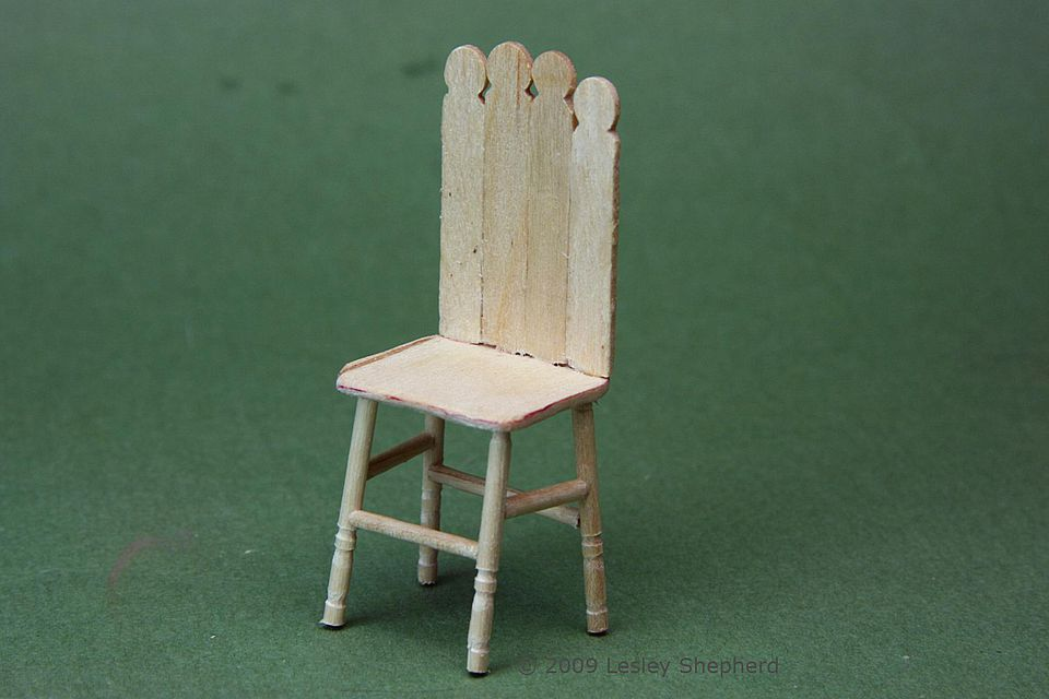 A dolls house scale child's chair made from toothpicks and wooden stir sticks.