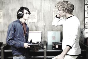 Two young men listening to headphones in record store
