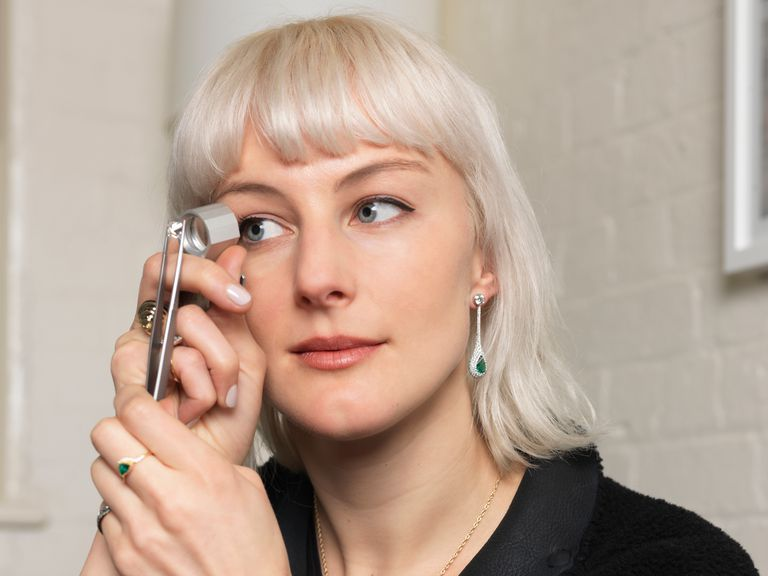 A woman using a jeweler's loupe