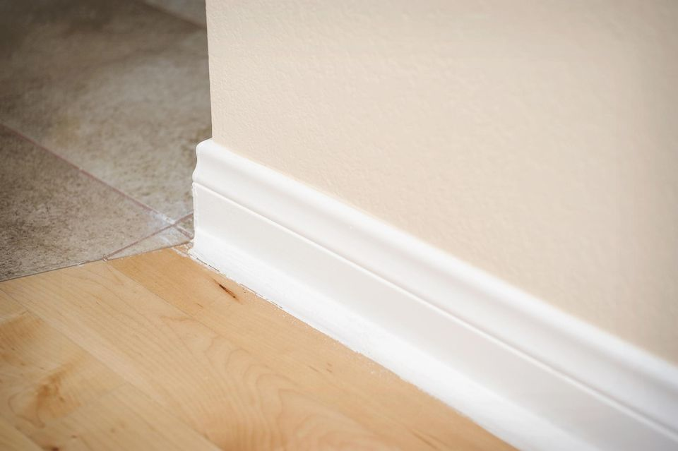 White baseboard along hardwood floor