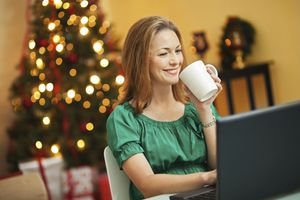 A woman drinking coffee at her computer on Christmas.