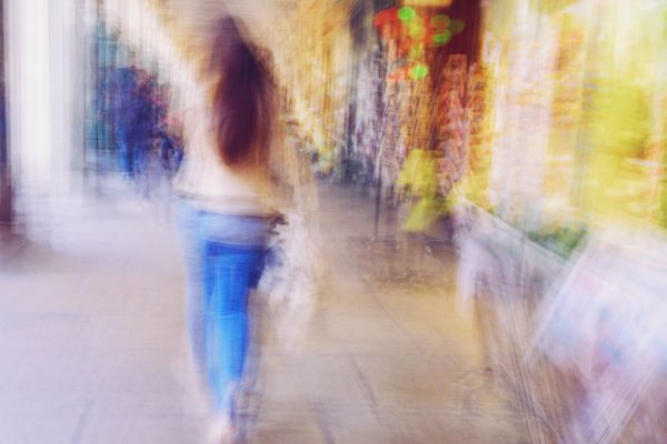 Blurred Motion Of Woman Walking On Street