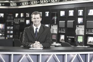 A news anchor at the desk.