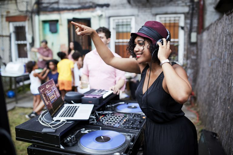 Mixed Race dj playing music at party in backyard