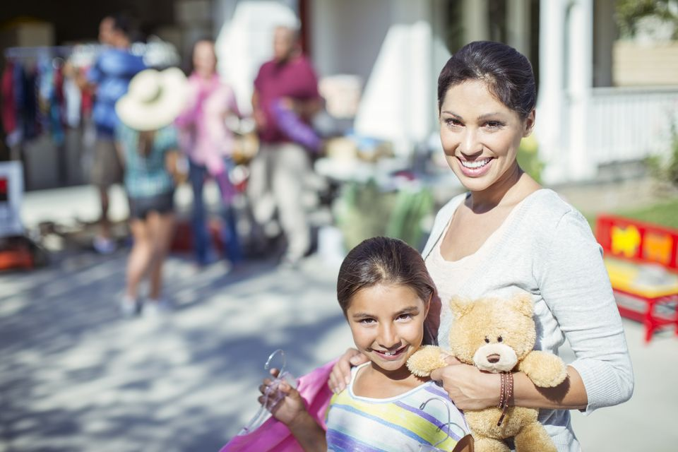 Portrait of mother and daughter shopping for toys at yard sale