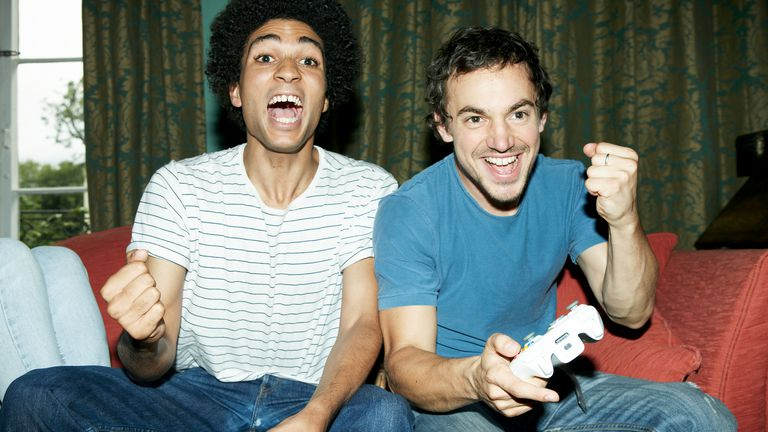 Two men wearing t-shirts and sitting on a lounge playing video games on an Xbox console
