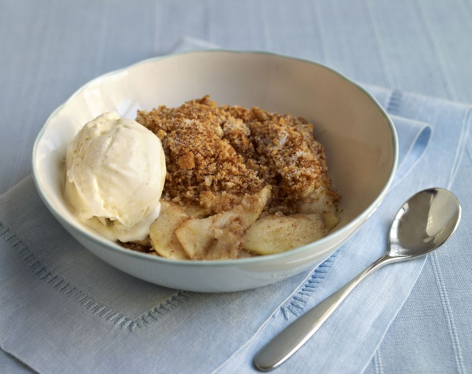 Apple Brown Betty in a bowl, spoon nearby