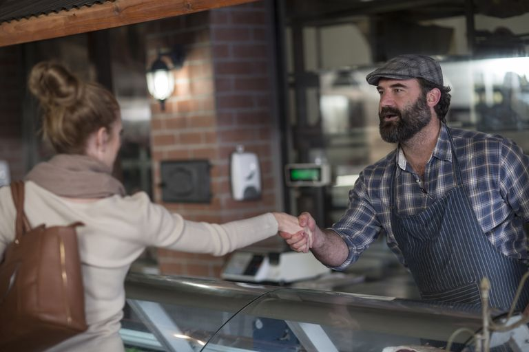Butcher shaking hands with client in butchery