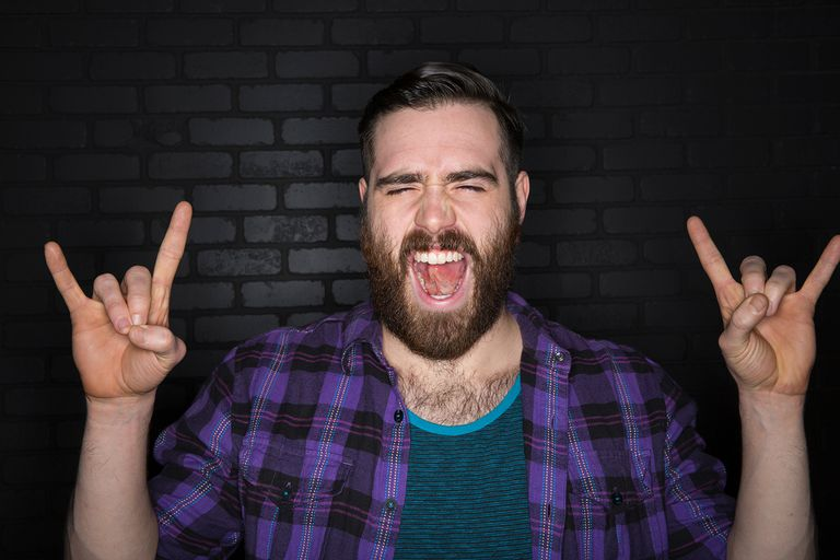 Portrait of bearded brunette man gesturing horn sign.