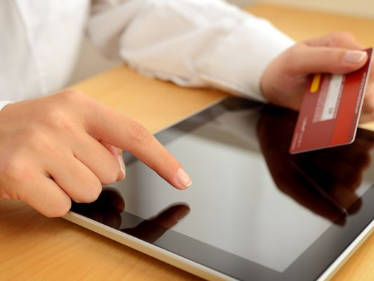 A person with a credit card and tablet