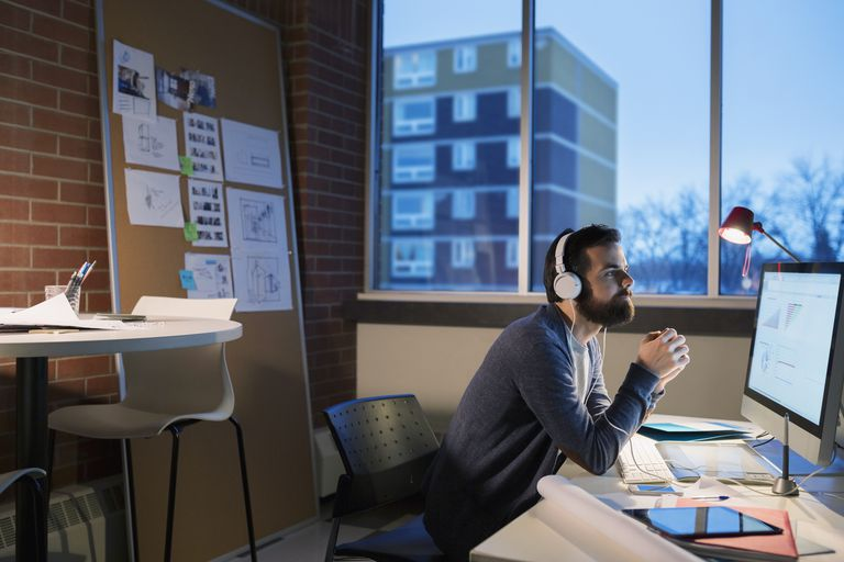 Graphic designer with headphones working late at computer