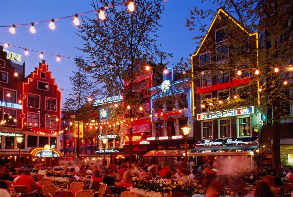 Courtyard with strings of lights and lit up restaurants in Amsterdam