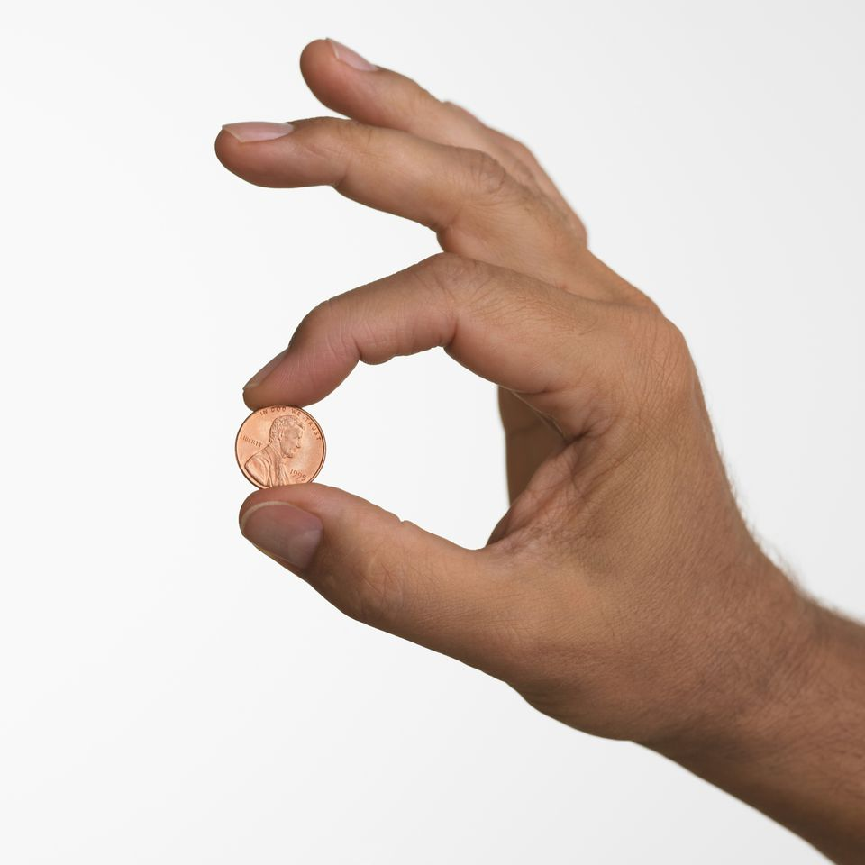 Hand Holding Penny 73448809