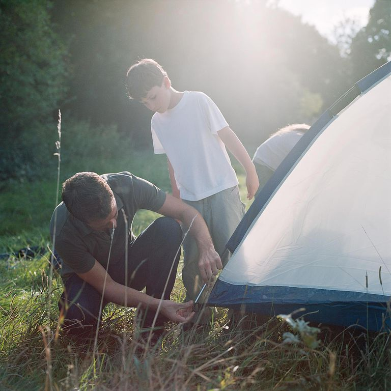 Father and son erecting a tent