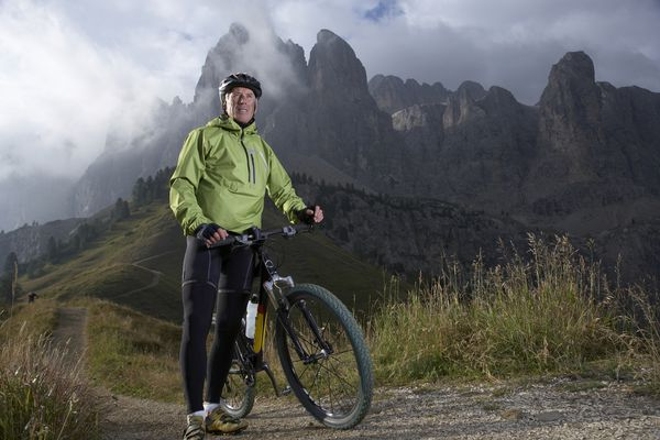 Man with a bike in front of a mountain.