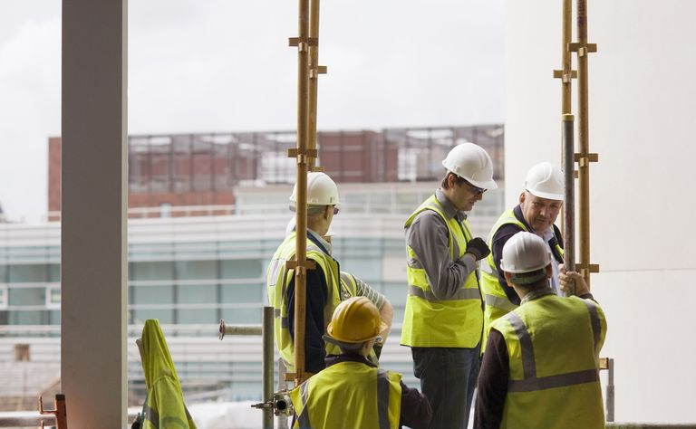 Workers on construction site discuss.