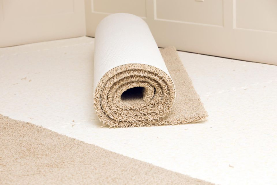 Carpet roll on pad in a bedroom awaiting installation