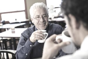 Two men chatting while drinking coffee at work