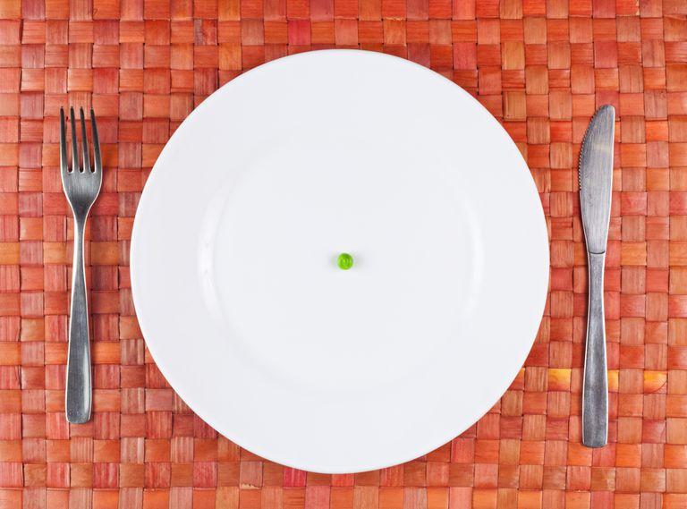 a single pea on a white plate