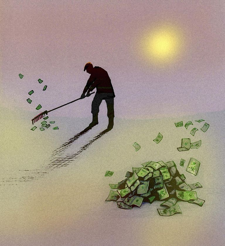 Man raking up piles of money banknotes