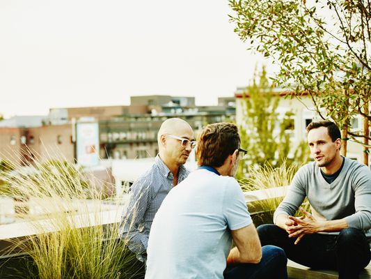 Three colleagues sitting on terrace of office building on summer evening having informal meeting