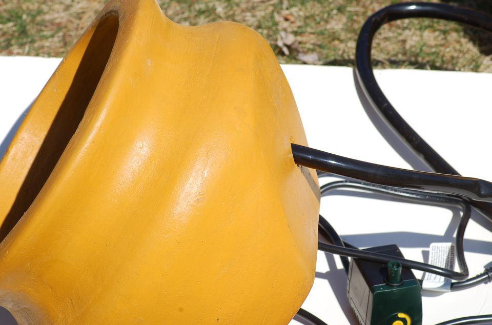 Clay, tilted pot with pump and tubing for fountain.