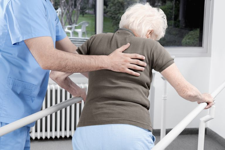 Health worker assisting a disabled woman in walking