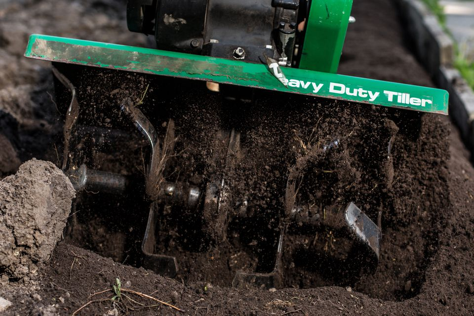 Small rototiller being operated, showing the tines digging into the earth.