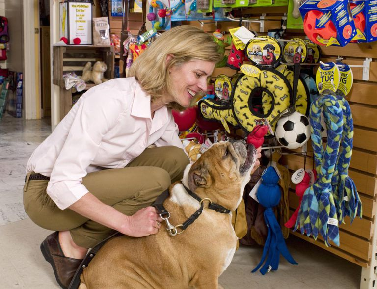 Woman with her dog shopping in pet store