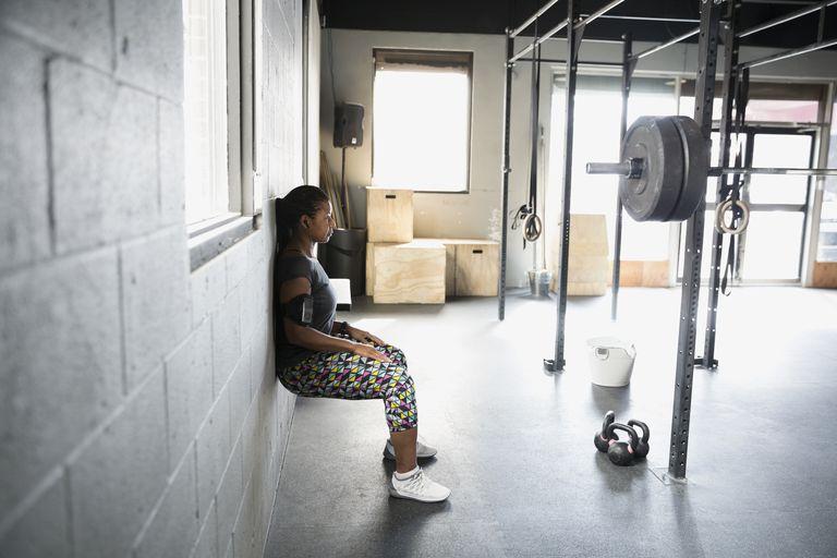 Woman doing wall squats at gym