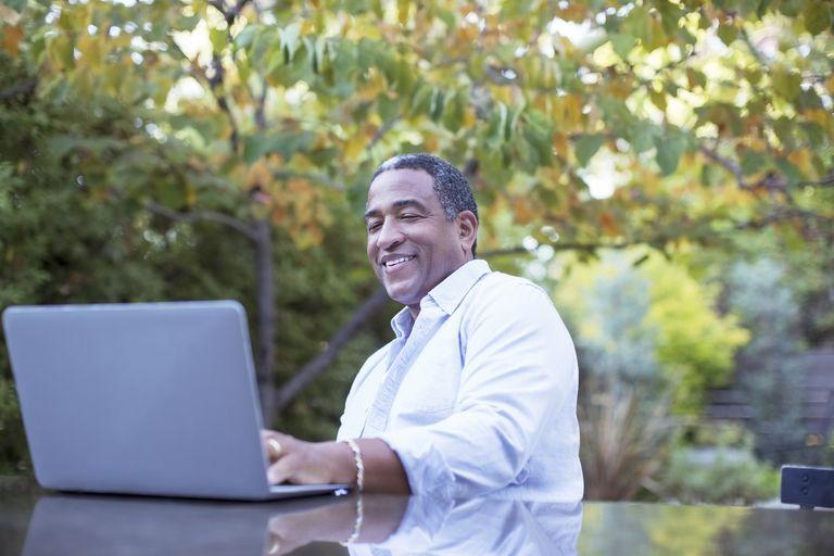 Senior man using laptop at patio table