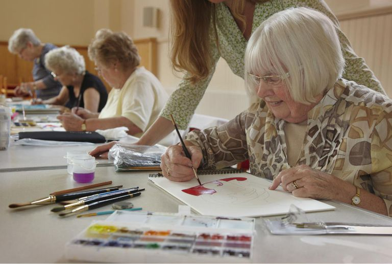 Senior woman receiving tuition in an art class