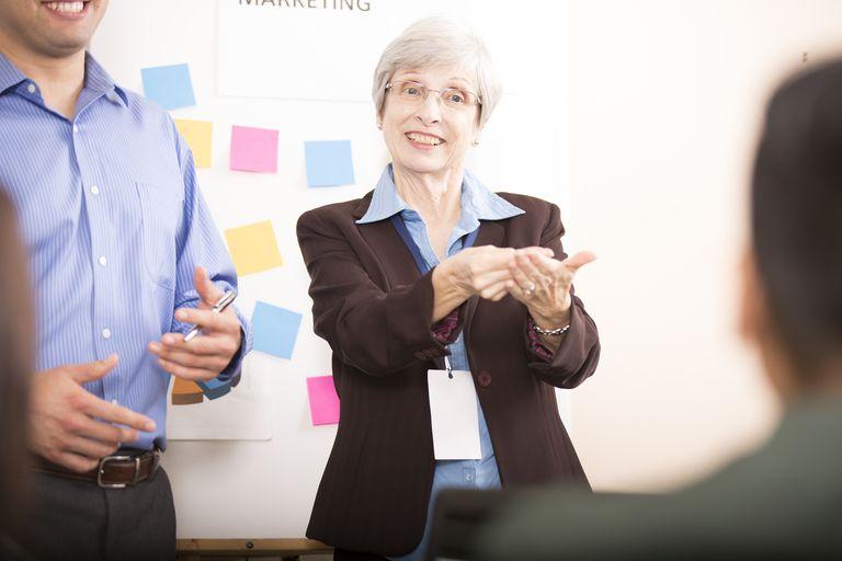 Interpreter signing during business meeting.