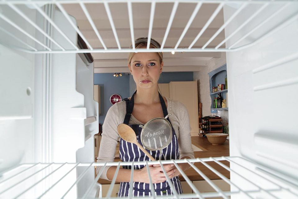 Woman looking into an empty fridge wearing an apron