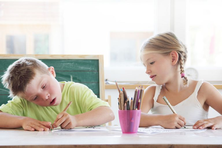 Children sitting at desk drawing with coloured pencils