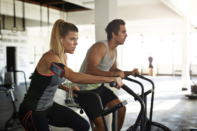 Woman & man working out on crosscycle at gym