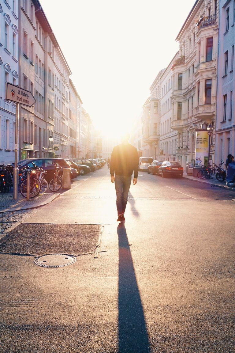 Man Walking On City Street Against Bright Sun