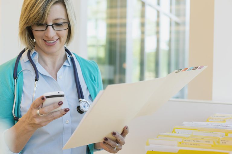 Female doctor holding file folder while using mobile phone in clinic
