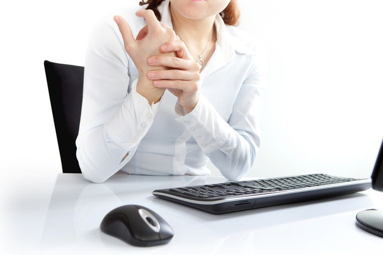 A woman at a desk experiencing discomfort