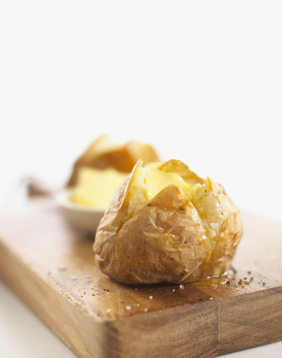 A potato with butter, salt and pepper, on a wooden chopping board, close-up